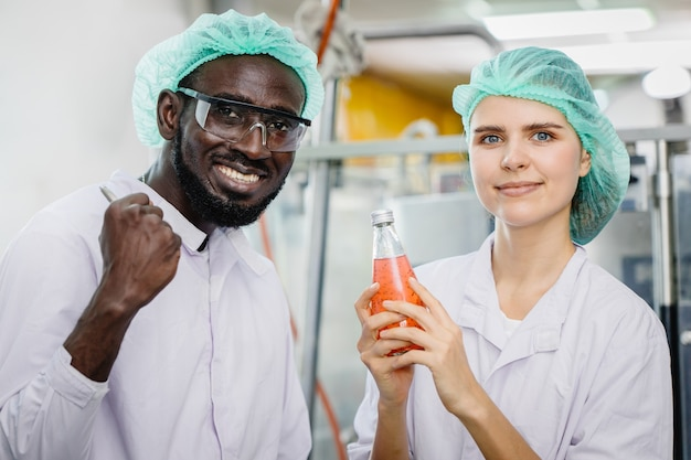 Portrait d'un travailleur de race mixte dans une usine de nourriture et de boisson travailleur heureux ensemble regardant la caméra et le sourire