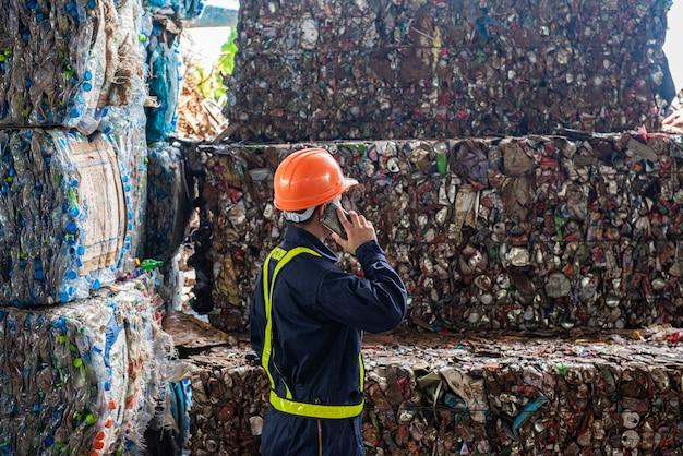 Portrait de travailleurs asiatiques de génie industriel avec un tas de bouteilles en plastique à l'usine