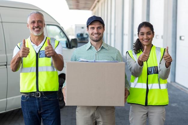 Portrait de travailleurs posent avec les pouces vers le haut près d'un livreur