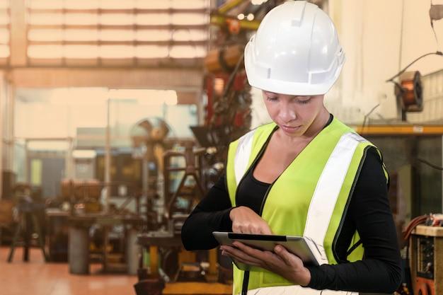 Portrait d'une travailleuse au beau visage et portant une tenue de travail et un casque de sécurité