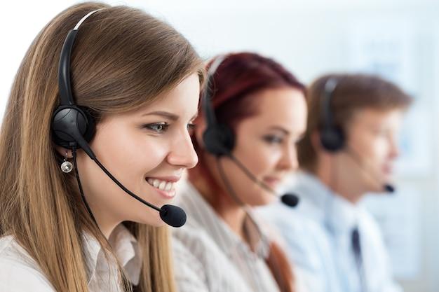 Portrait de la travailleuse du centre d'appels accompagnée de son équipe. souriant opérateur de support client au travail. concept d'aide et de support