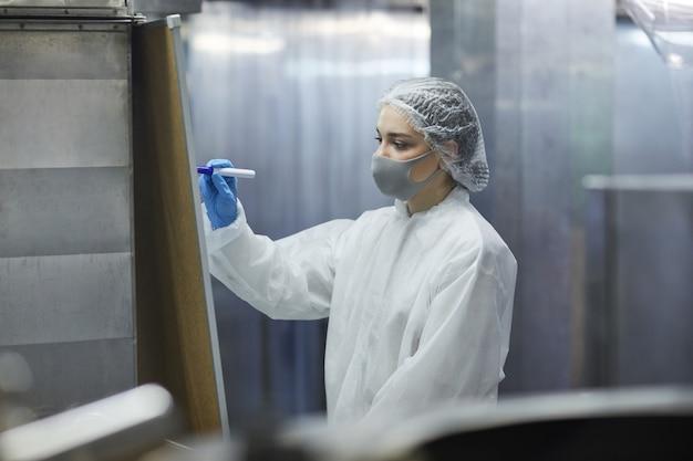 Portrait d'une travailleuse portant un masque et une combinaison de protection tout en écrivant à bord dans l'atelier de l'usine, espace de copie
