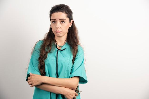 Portrait d'une travailleuse de la santé posant sur un mur blanc.