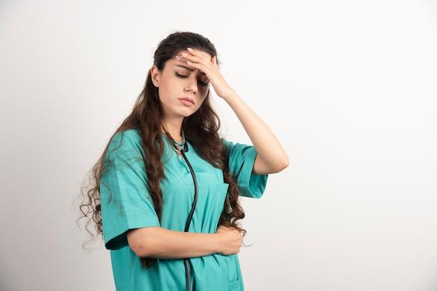 Portrait d'une travailleuse de la santé touchant sa tête sur un mur blanc.