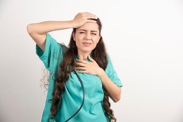 Portrait d'une travailleuse de la santé touchant sa tête.