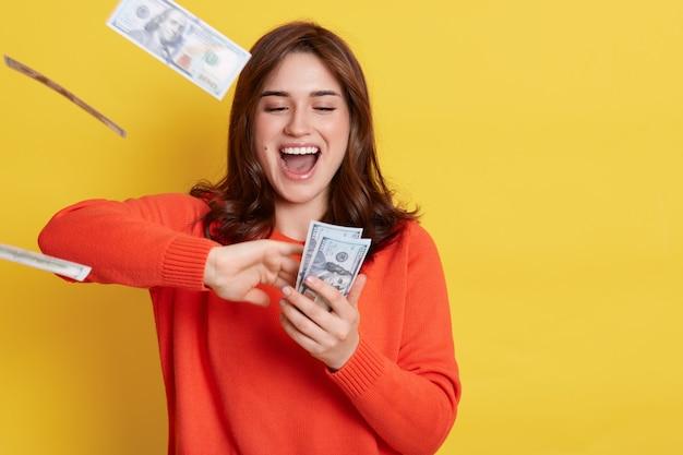 Portrait de très heureuse jeune femme de race blanche jetant des billets d'argent, criant quelque chose joyeusement, ayant excité l'expression du visage, garde la bouche ouverte, se tient isolé sur un mur jaune.