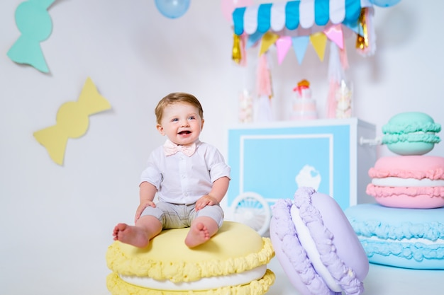 Portrait d'un très joli petit garçon assis sur un gros macaron et souriant.