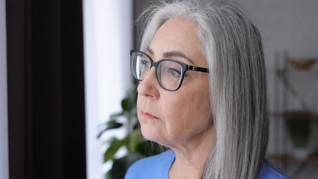 Portrait de triste belle femme aux cheveux gris âgée.