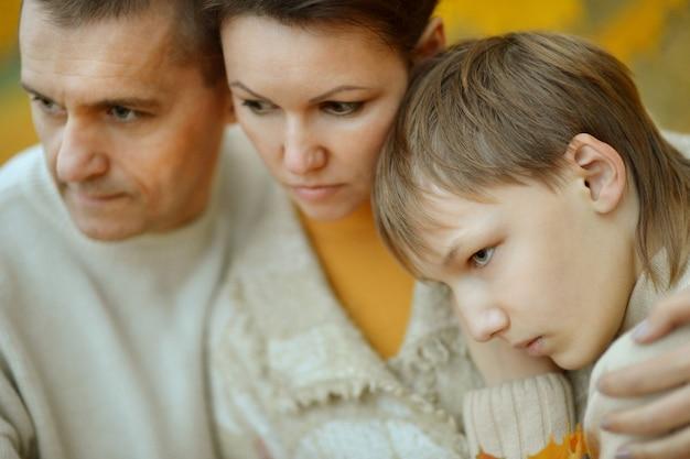 Portrait d'une triste famille de trois personnes sur la nature