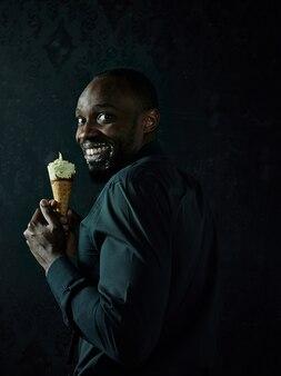 Portrait de triste homme afro-américain tenant la crème glacée sur studio noir
