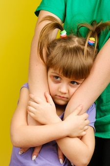 Portrait de triste petite fille caucasienne avec des nattes et des ecchymoses sous les yeux