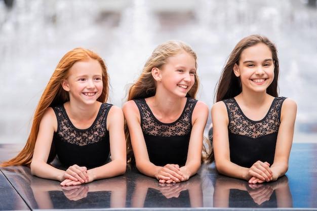 Portrait de trois adolescentes aux cheveux dénoués, blonde, rousse et brune summer on street. les vlos se développent avec le vent.