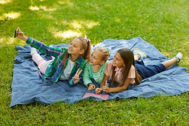 Portrait de trois adolescentes prenant selfie ensemble en position couchée sur l'herbe verte dans le parc à l'extérieur éclairé par la lumière du soleil