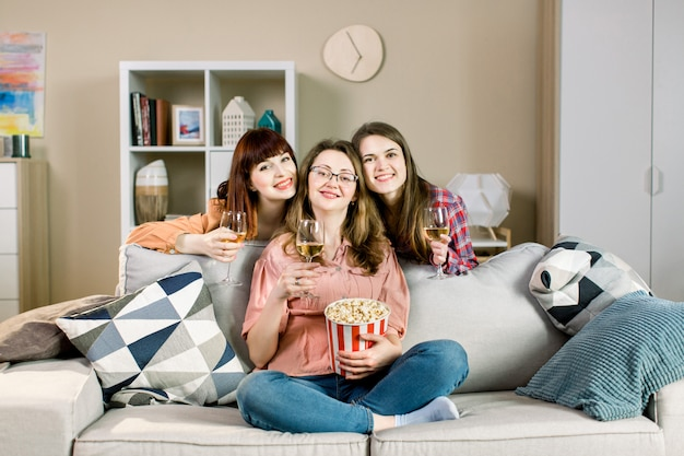Portrait de trois amis de jeunes filles gaies avec des bols de pop-corn et du vin, près du canapé élégant à la maison.