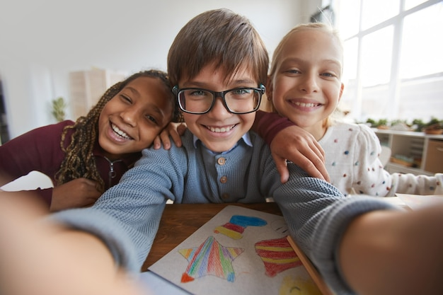 Portrait de trois enfants heureux souriant à la caméra tout en prenant une photo de selfie à l'école