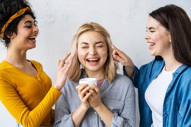 Portrait de trois femmes heureuses riant et jouant avec une crème hydratante