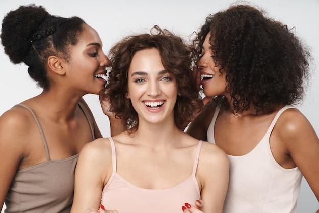Portrait de trois femmes multiethniques joyeuses se tenant ensemble et parlant de secrets dans les oreilles d'une fille isolées sur un mur blanc