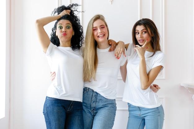 Portrait de trois femmes multiethniques séduisantes debout ensemble et souriant à la caméra isolée sur fond blanc
