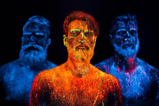 Portrait de trois hommes barbus peints dans des poudres fluorescentes.