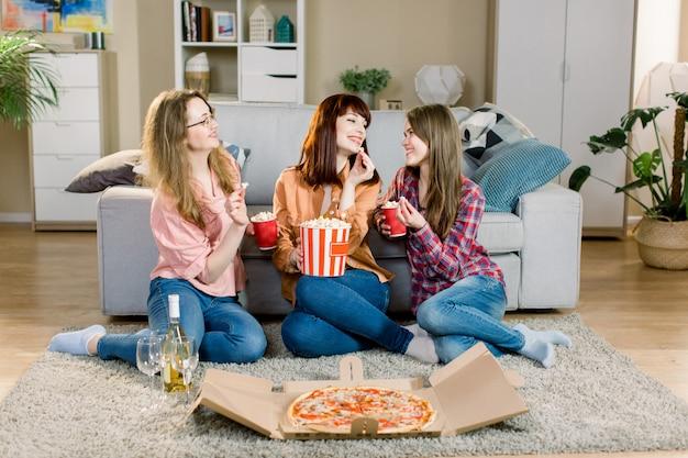 Portrait de trois jeunes amies gaies avec des bols de pop-corn, de la pizza et du vin, assis sur le sol près du canapé élégant à la maison