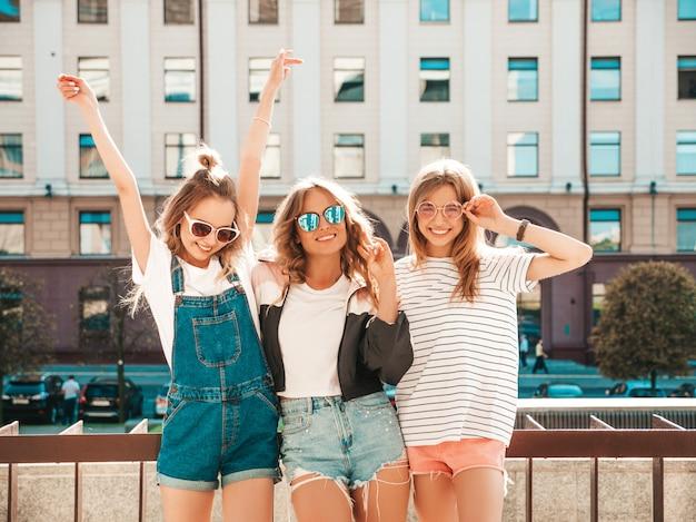 Portrait de trois jeunes belles filles hipster souriantes dans des vêtements d'été à la mode. sexy, insouciant, femmes, poser, rue, positif, modèles, amusant, lunettes soleil, étreindre