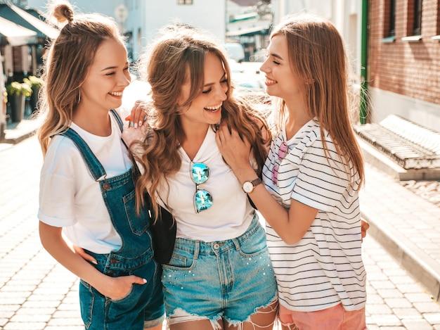 Portrait de trois jeunes belles filles hipster souriantes dans des vêtements d'été à la mode. sexy, insouciant, femmes, poser, rue, positif, modèles, amusant