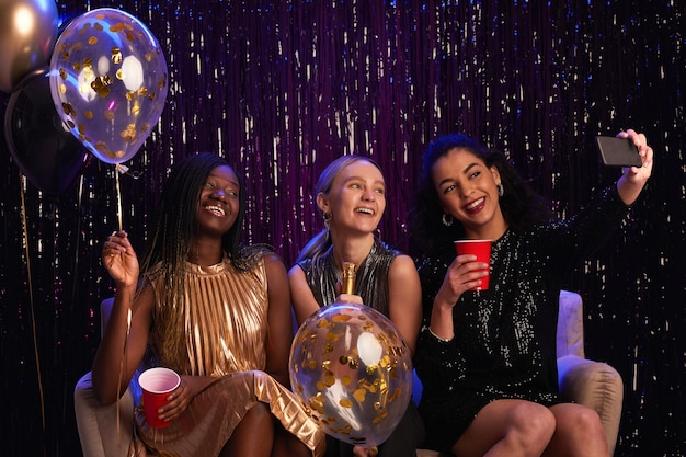 Portrait de trois jeunes femmes prenant selfie photo à la fête tout en portant des robes étincelantes