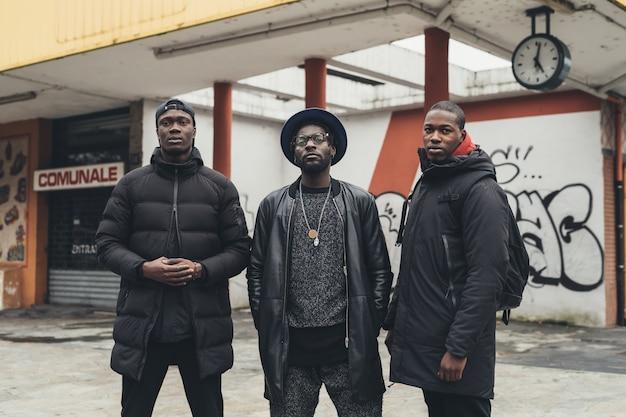 Portrait de trois jeunes hommes africains posant en plein air dans la rue