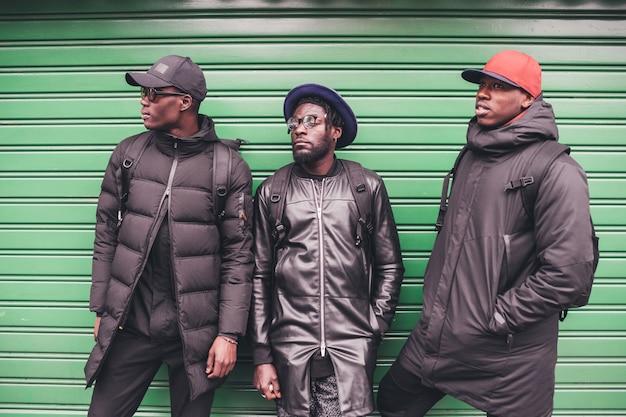 Portrait de trois jeunes hommes africains s'appuyant contre un volet roulant