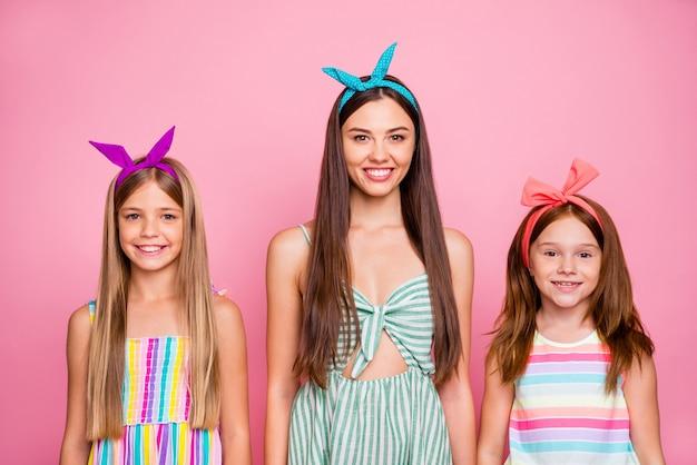 Portrait de trois jolies dames à la recherche de robes lumineuses souriant isolé sur fond rose