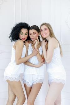 Portrait de trois magnifiques jeunes femmes multiraciales avec différents types de peau. filles debout en rang et regardant dans des directions opposées. concept d'amis divers.