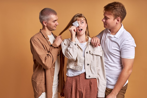 Portrait de trois personnes, femme tenant le préservatif dans les mains, avec deux hommes isolés en studio