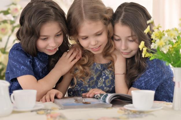Portrait de trois petites filles mignonnes lisant le magazine