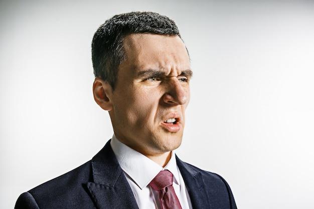 Portrait de trois quarts d'un homme d'affaires avec un visage dégoûté.