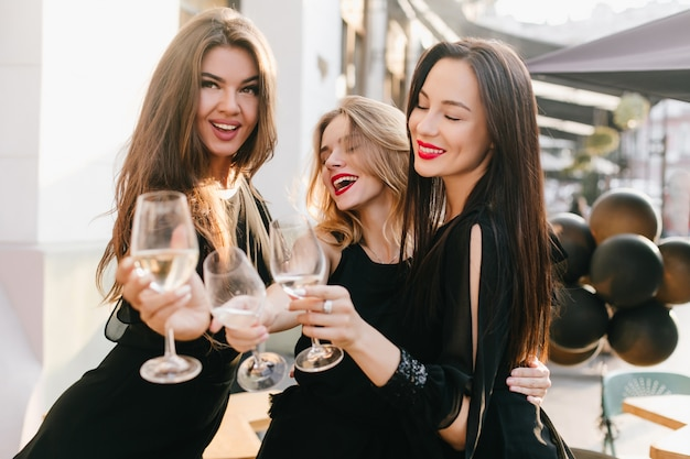Portrait de trois sœurs en tenue noire célébrant un événement important avec du champagne