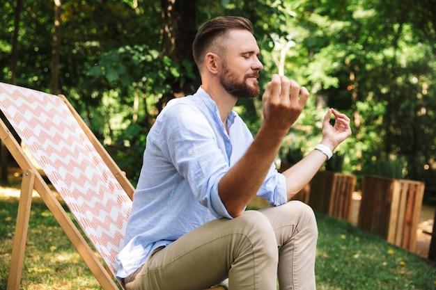 Portrait de type caucasien détendu assis dans une chaise longue avec les yeux fermés et le geste d'yoga, pendant le repos dans le parc verdoyant