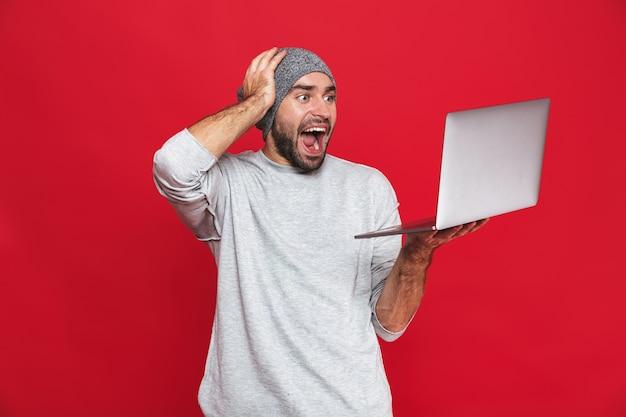 Portrait de type heureux 30 s en tenue décontractée se réjouissant tout en tenant un ordinateur portable en argent isolé