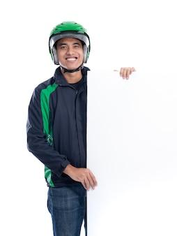 Portrait d'uber rider avec casque tenant un tableau blanc vierge