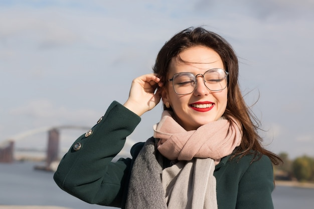 Portrait urbain d'une belle dame brune posant dans la ville, portant des lunettes, un manteau vert et une écharpe