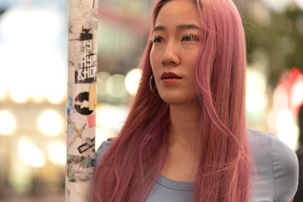 Portrait urbain de jeune femme aux cheveux roses