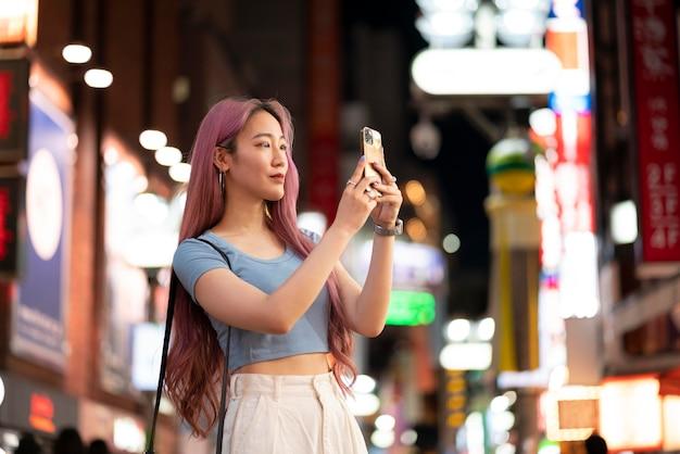 Portrait urbain de jeune femme aux longs cheveux roses