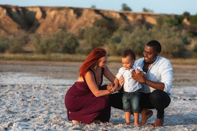 Portrait de vacances en famille. parents souriants avec enfant en bas âge. jeune famille métisse se détendre à la plage par une belle journée d'été