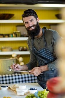Portrait de vendeur écrit sur le presse-papiers au comptoir