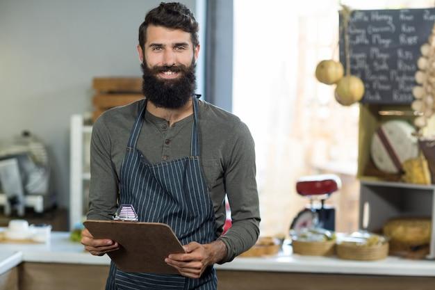 Portrait de vendeur tenant le presse-papiers au comptoir