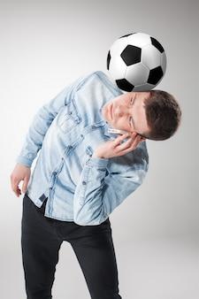 Le portrait de ventilateur avec ballon, tenant le téléphone sur blanc