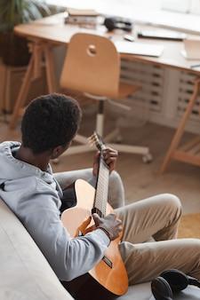 Portrait vertical à angle élevé de jeune homme afro-américain jouant de la guitare acoustique et assis sur le canapé à la maison