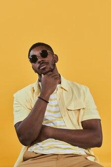 Portrait vertical d'un bel homme afro-américain portant des lunettes de soleil et regardant la caméra tout en pos...