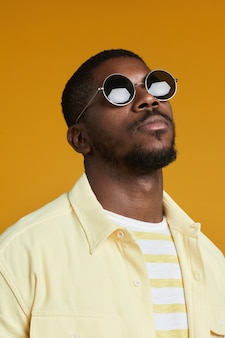 Portrait vertical d'un bel homme afro-américain portant des lunettes de soleil tout en posant contre un bac jaune...