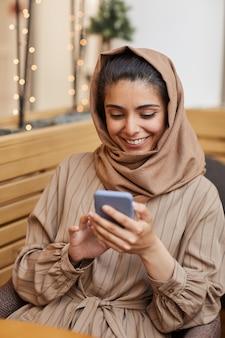Portrait vertical de la belle femme du moyen-orient souriant joyeusement tout en regardant l'écran du smartphone au café