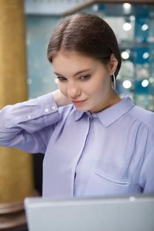Portrait vertical d'une belle femme essayant des boucles d'oreilles à la bijouterie